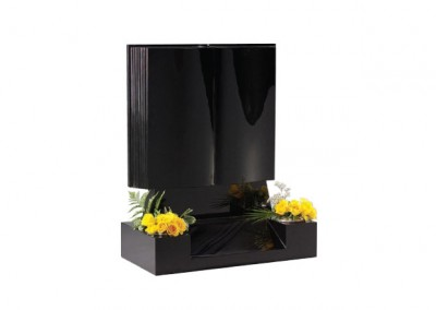 Black granite book memorial with shaped back and front and centre splay base.
