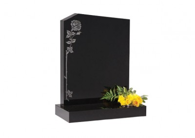 Black granite headstone with peon top with etched single climbing rose ornament.