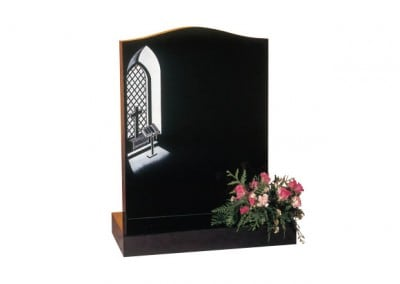 Black granite headstone with etched and painted 'church window and bible' design.