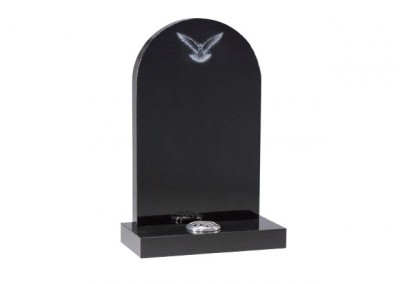 Black granite with etched dove design and rounded top.