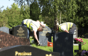 Two workmen carrying out maintenance on cemetery headstones